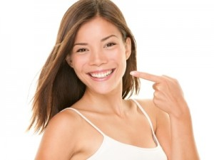 Dental teeth - perfect smile woman pointing at toothy smile looking happy at camera